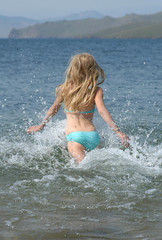 young girl running to the water