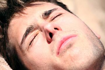 jeune homme a la plage ébloui au soleil