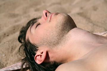 jeune homme a la plage bronzant au soleil