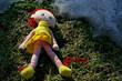 rothaarige Puppe im Gras und Schnee