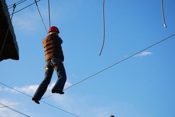 courageous woman standing on a steel wire taking a
