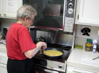 senior female cooking eggs