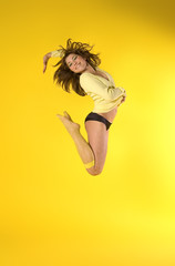happy girl jumping high on yellow