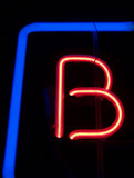 """letters"": neon red ""b"" with blue frame"