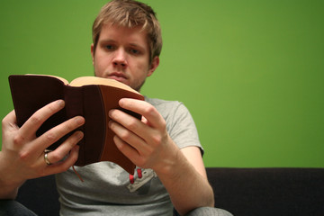 young man reading small bible