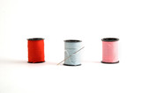 3 sewing thread spools and a needle. poster