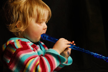 blond girl playing blue flute