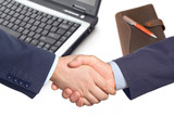 business handshake  with a laptop and a notepad poster