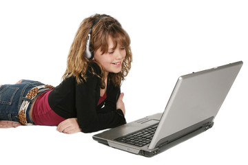 young girl listening to music on laptop