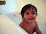 baby girl playing in bathtub poster