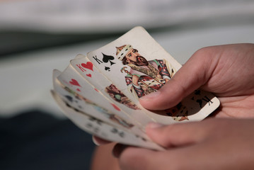 a hand holding playing cards