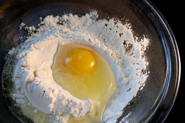 raw egg in a bowl of flour