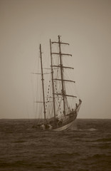 three-masts sailing ship in stormy day