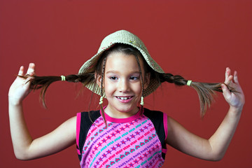 girl with a hat holding tresses
