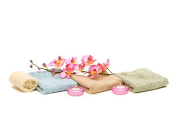 spa towels, candles, loofah and pink orchid
