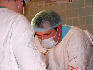 splashes of blood on surgeon's arms