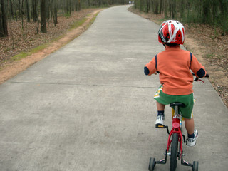 little boy learning to ride bicycle