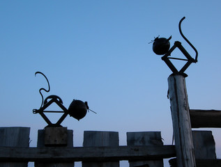 two mechanical cats on a fence.