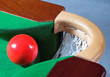 a red snooker ball balanced at a corner pocket