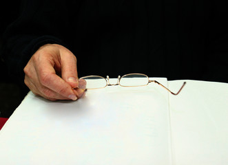 the hand with glasses and a paper