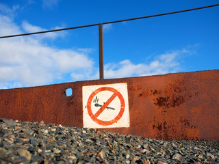 rusty no fire and smoking sign board in an open-cast mine