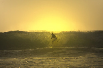 sunset surfer cross a wave