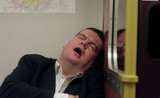 man asleep on train poster
