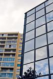 contraste entre immeuble de bureau et habitations poster