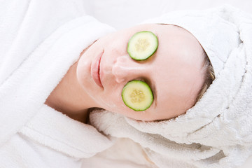woman with a facial mask and cucumber on her face