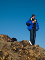 man thinking on the mountain top with blue sky