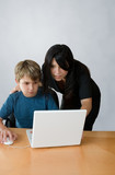 adult assisting child on computer poster