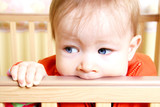 baby in bitting on crib poster