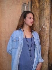 pretty teenage girl by an adobe wall