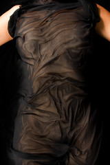anonymous women's naked body covered by transparent black cloth.