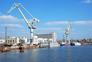 shipbuilding cranes and some sea ships near a pier