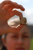 girl holds stacked british coins by pound