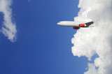 airplane partly emerging from out of giant cloud poster