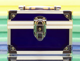 dark blue steel small suitcase with the lock on a multi-coloure poster