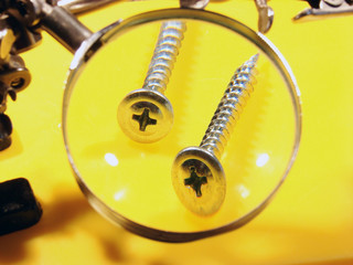 two screws under a magnifier on a yellow background