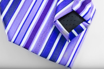 closeup of navy blue and purple stripe business tie on white bac