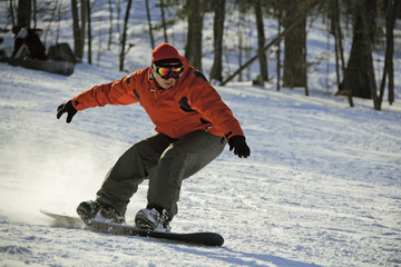 sliding snowboarder on flank of hill