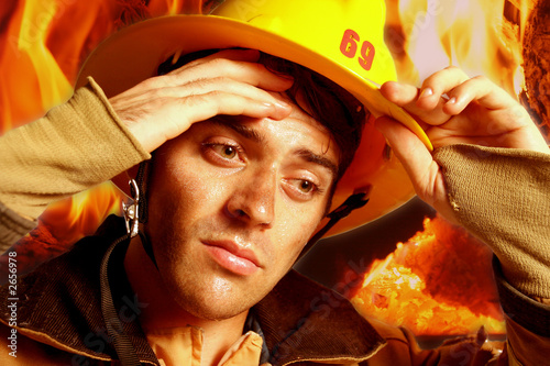 vertical close-up of a firefighter in his gear wiping sweat from