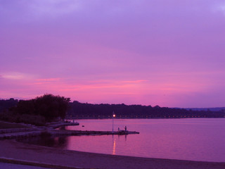 beach and dock in the sunset with a purple sky