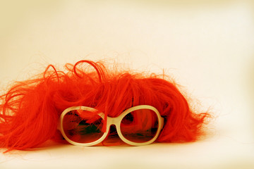 isolated red wig toupee and sun glasses