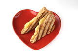 sandwich with melted cheese on heart shape plate poster