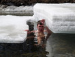 young man swimming among ice floats