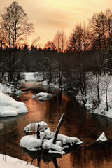 sunset in a wood on the winter river