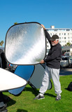 teaching the use of reflectors for an outdoor photoshoot poster