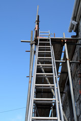 a builder's ladder and scaffolding on a house bein
