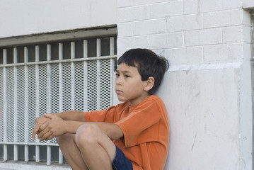 boy sitting against wall